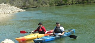 man and lady in kayaks on river