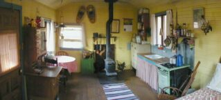 Line Camp Cabin interior with bed, antique stove, pot-belly stove fireplace and other furniture