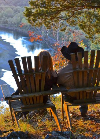 man and lady sitting in chairs viewing river below