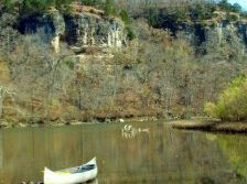 canoe along river with bluff in background