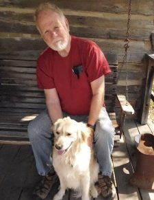 man with holding dog sitting in front of him