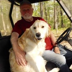 man with arm around dog in vehicle