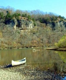 canoe alongside river with bluffs in background