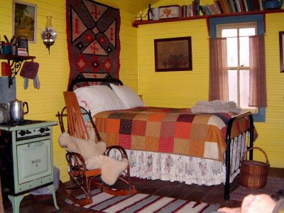 bed in Line Camp Cabin covered with quilty, rocker and old kitchen stove