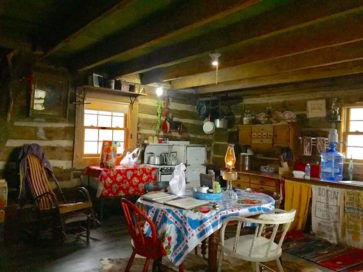 interior of Aunt Phoebe's cabin with table, chairs, rocker
